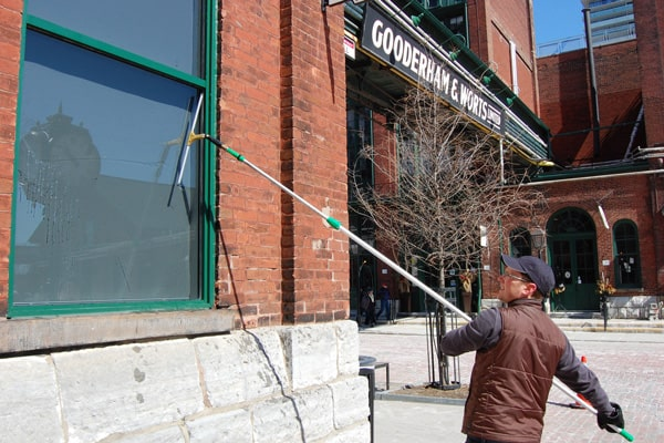 Man cleaning a window in the Distillery District in Toronto